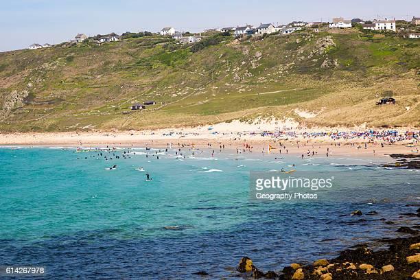 Coastal scenery with busy crowded sandy beach, Sennan Cove, Land's End, Cornwall, England, UK.