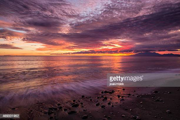 coastal sunrise on the beach in amed village in bali - sunset beach stock photos and pictures