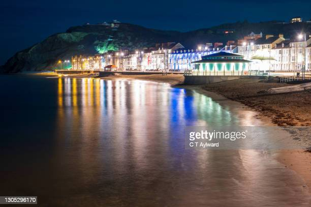 coastal town lights at night - wales stock pictures, royalty-free photos & images