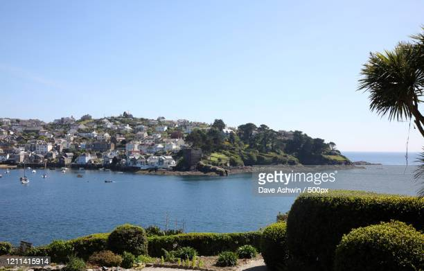 coastal town with harbor and sailboats in sea, polruan, cornwall, england, united kingdom - dave ashwin stock pictures, royalty-free photos & images