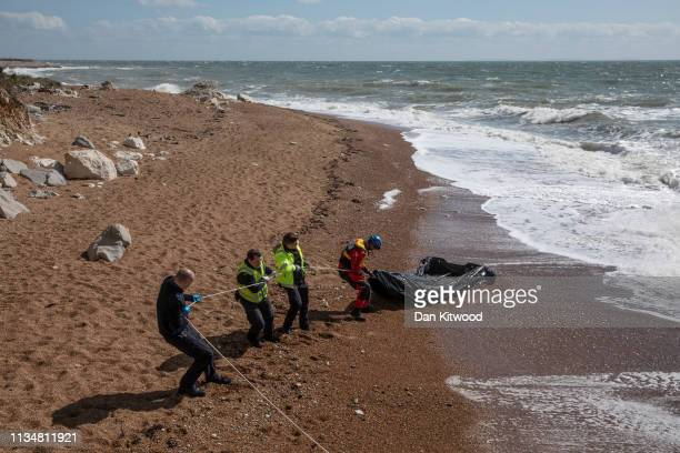 Coastguard and Border Force officials drag an inflatable rib from the sea near Samphire Hoe on April 4 2019 in Dover England Two separate incidents...