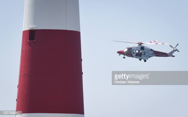 Coastguard helicopter passes Portland Bill lighthouse during the search for a missing snorkeler on May 28, 2020 in Portland, England. HM Coastguard...