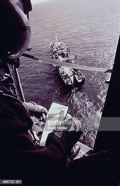 Coastguard observer checking fishing vessel from air (B&W)