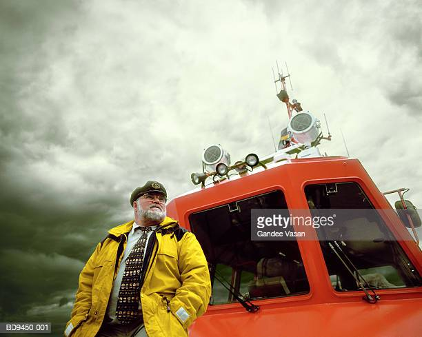 coastguard standing by cabin of lifeboat - coast guard stock pictures, royalty-free photos & images