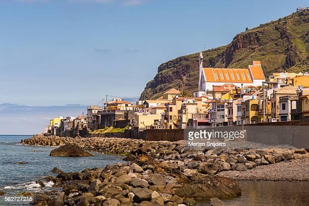 coastline below village of paul do mar with church - merten snijders stockfoto's en -beelden