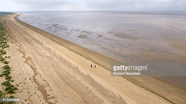 coastline dog walkers - norfolk england stock pictures, royalty-free photos & images
