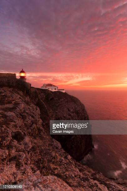coastline landscape at sunset with reddish sky and a lighthouse lit on the cape of san vicente, portugal - sagres foto e immagini stock