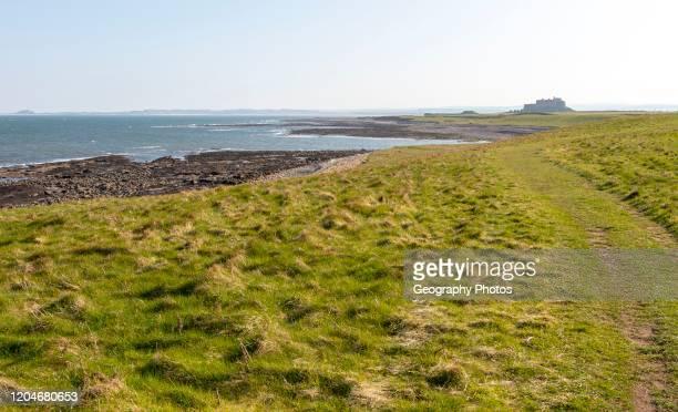 Coastline landscape scenery looking south towards Farne Islands and castle, Holy Island, Lindisfarne, Northumberland, England, UK.