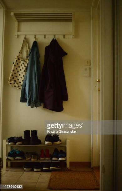 coat and jacket hanging on a rack over a shelf with shoes in an entrance - kristina strasunske stock pictures, royalty-free photos & images