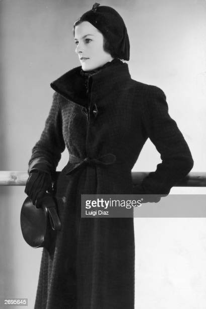 Coat designed by Elsa Schiaparelli in brown and beige wool check. The winter coat has a stand-up collar, tie belt and large unusually shaped buttons...