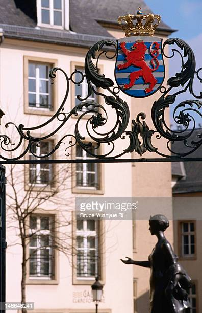 coat of arms of grand-ducal of luxembourg on iron gate, with grand duchess charlotte monument in clairefontaine square behind. - grand duchess stock pictures, royalty-free photos & images