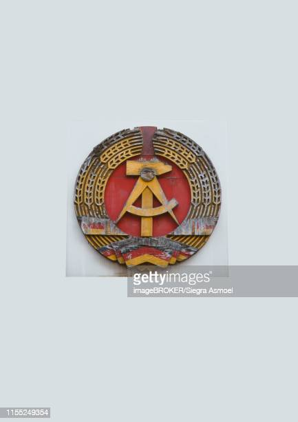 coat of arms of the former gdr on the wall, checkpoint charly, berlin, germany - east germany stock pictures, royalty-free photos & images