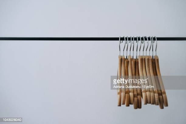 coathangers hanging in rack against white background - clothes rack stock pictures, royalty-free photos & images