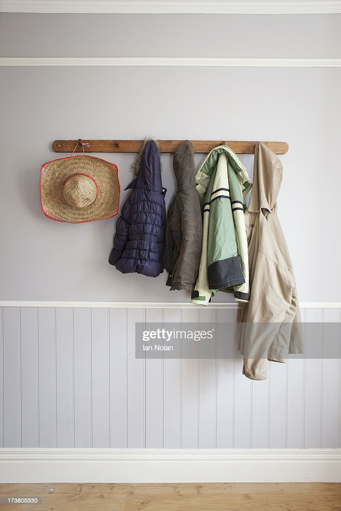 Coats and hat on coat rack : Stock Photo