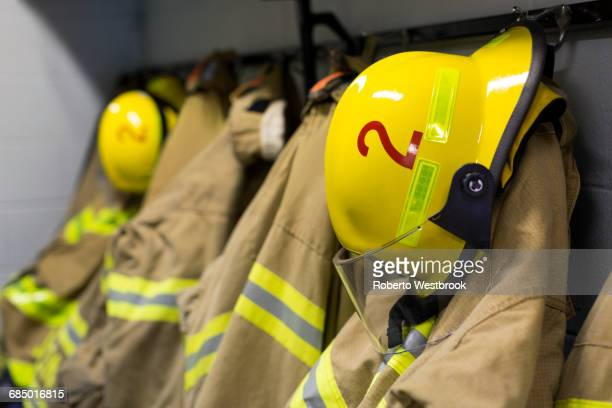 coats and helmets of fire fighters hanging on hooks - fire station - fotografias e filmes do acervo