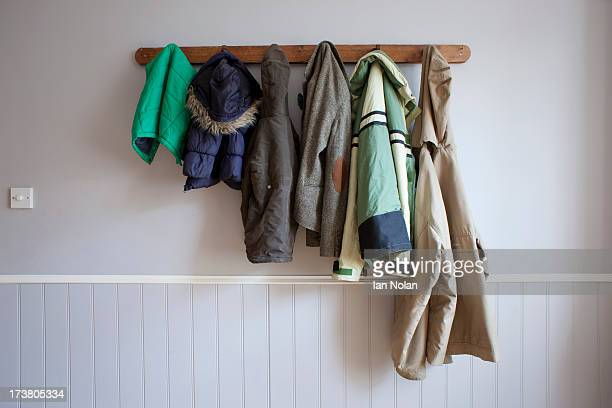 coats hanging on coat rack - coat stock pictures, royalty-free photos & images