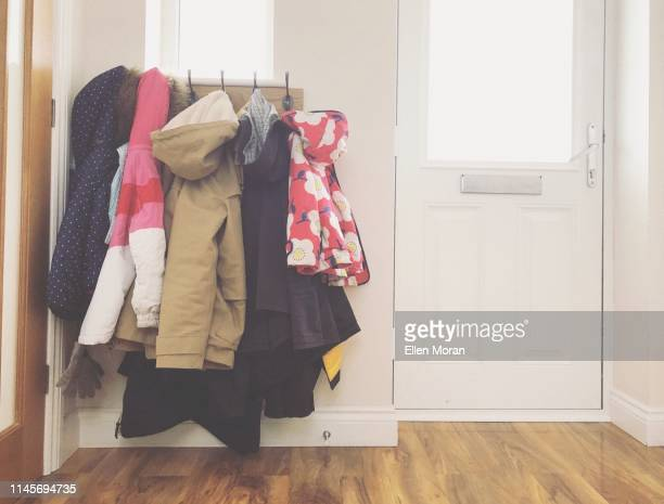 coats hanging on hooks. - coat stock pictures, royalty-free photos & images