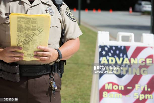 Cobb County Sheriff holds sample ballots outside the Cobb County West Park Government Center where voters line up to early vote on October 18 2018 in...