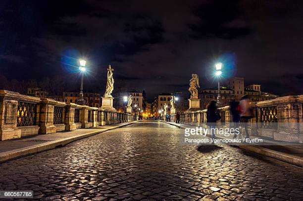 cobbled road at illuminated bridge against sky - vgenopoulos stock pictures, royalty-free photos & images