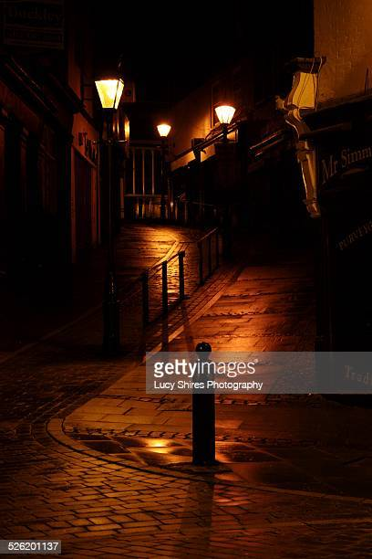 cobbled road at night, lit by street lights. - lucy shires stock pictures, royalty-free photos & images
