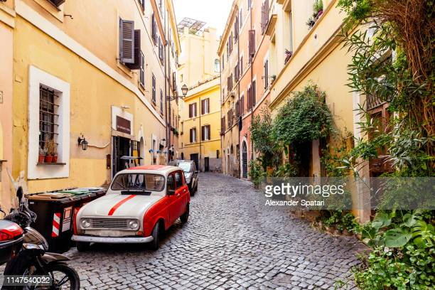 Cobbled street in Trastevere with old vintage car, Rome, Italy