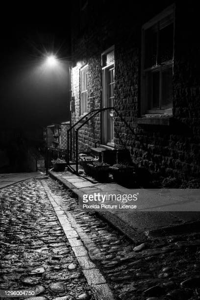 a cobbled wet street at night - cobblestone stock pictures, royalty-free photos & images