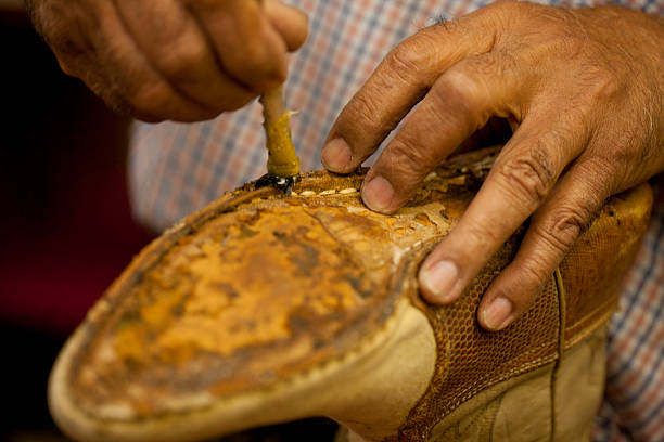 cobbler applying glue on sole of boot - old asian shoe maker stock pictures, royalty-free photos & images
