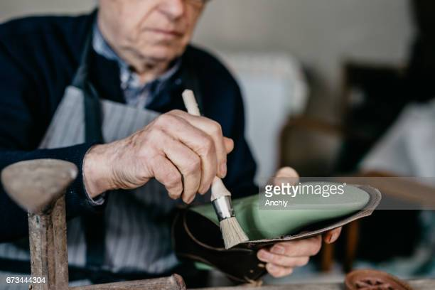 Cobbler holding a brush in hand