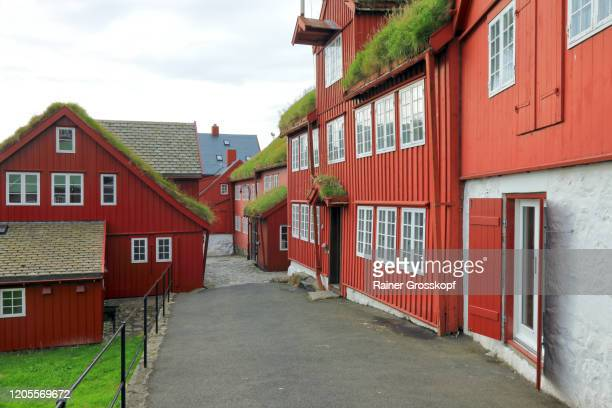 a cobblestone road through old wooden red buildings in the historic part of tórshavn - rainer grosskopf stock pictures, royalty-free photos & images