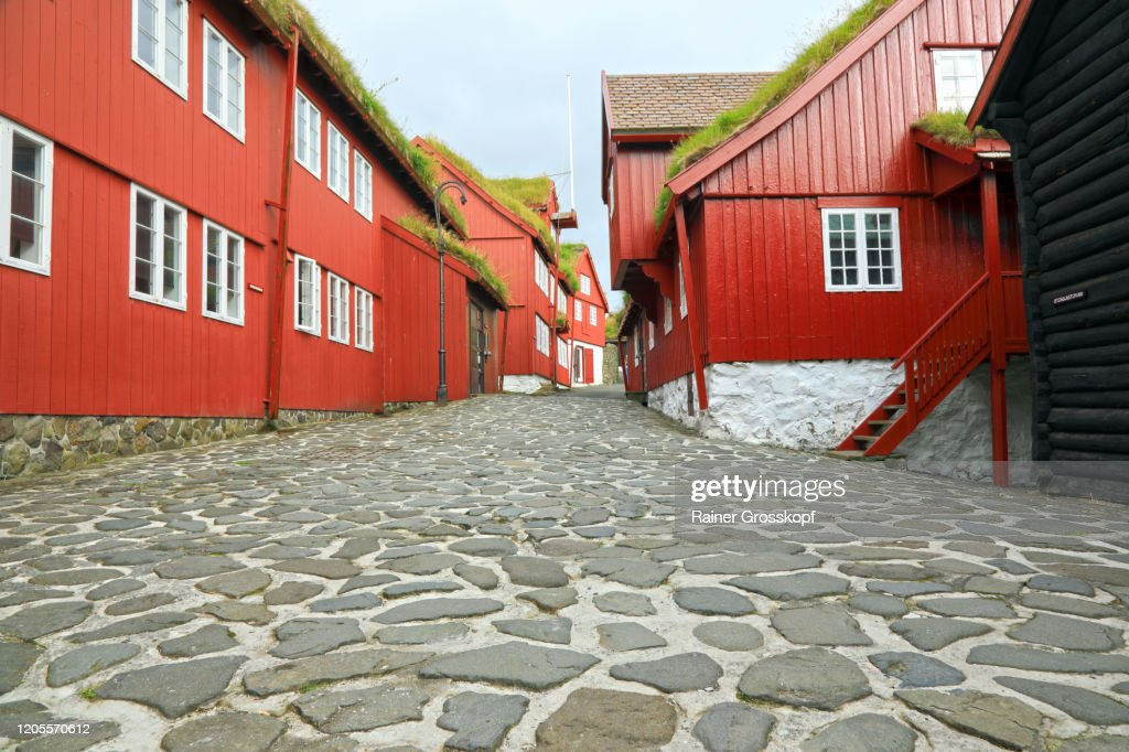 A cobblestone road through old wooden red buildings in the historic part of Tórshavn : Stock-Foto