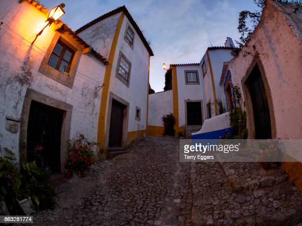 cobblestone street at sunset - leiria district stock photos and pictures