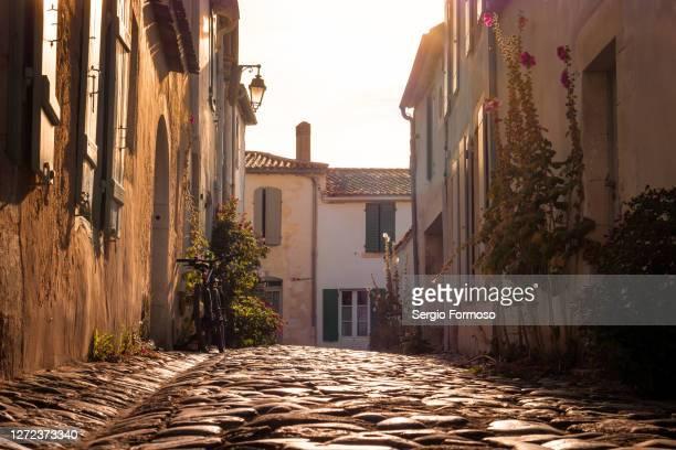 cobblestone street in saint-martin-de-ré, île de ré, france - village stock pictures, royalty-free photos & images
