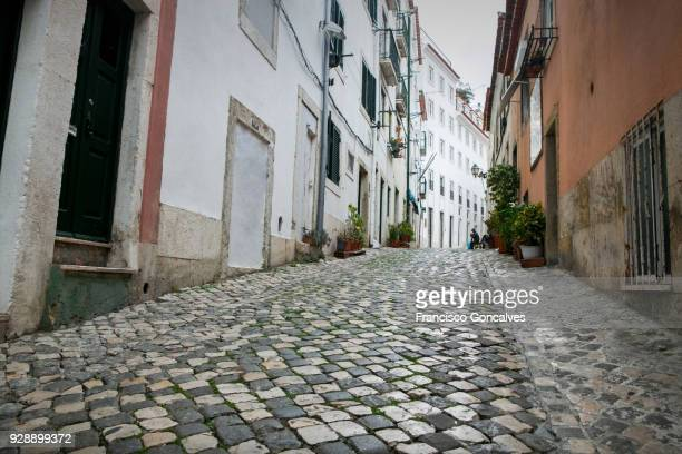 cobblestone street in the alfama district of lisbon - alfama stock photos and pictures
