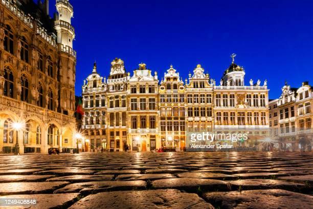 cobblestones and historical buildings at grand place, brussels, belgium - grote markt brussel stockfoto's en -beelden