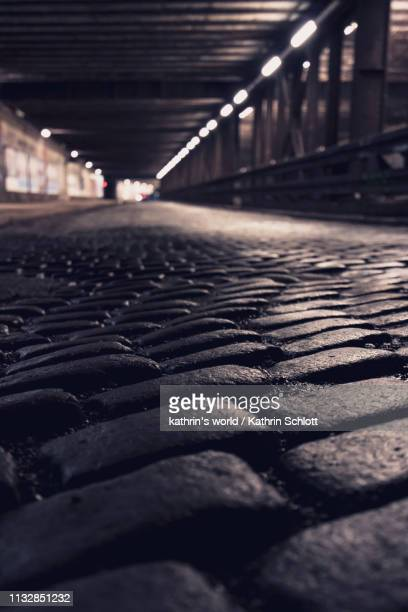 cobblestones in an underpass - straßenverkehr stock pictures, royalty-free photos & images
