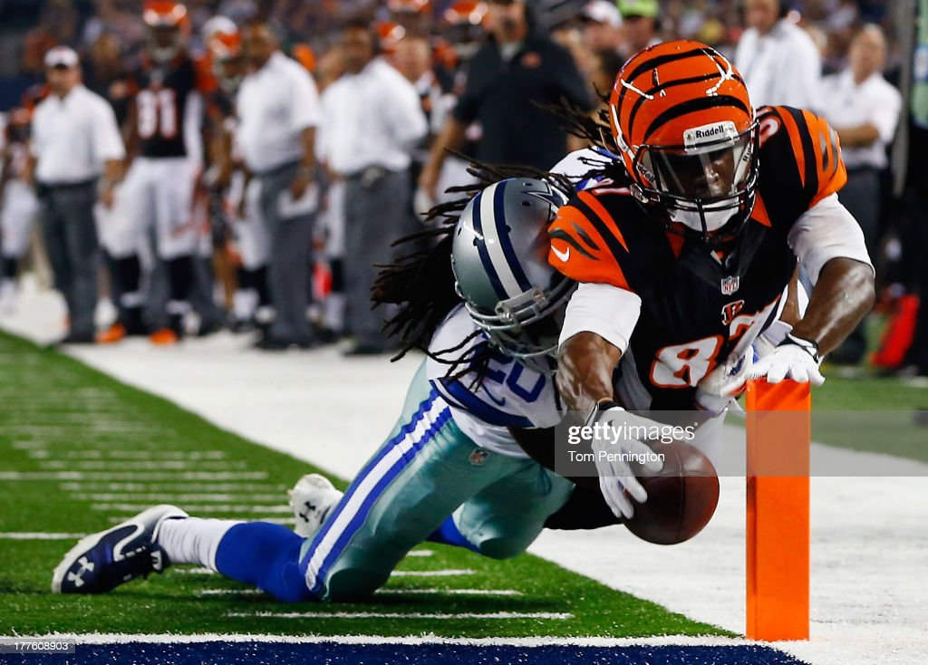 Cobi Hamilton #87 of the Cincinnati Bengals dives into the end zone to score a touchdown against B.W. Webb #20 of the Dallas Cowboys in the fourth quarter during a preseason game at AT&T Stadium on August 24, 2013 in Arlington, Texas.
