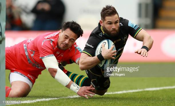 Cobus Reinach of Northampton Saints dives to score the first try despite the challenge from Denny Solomona during the Gallagher Premiership Rugby...
