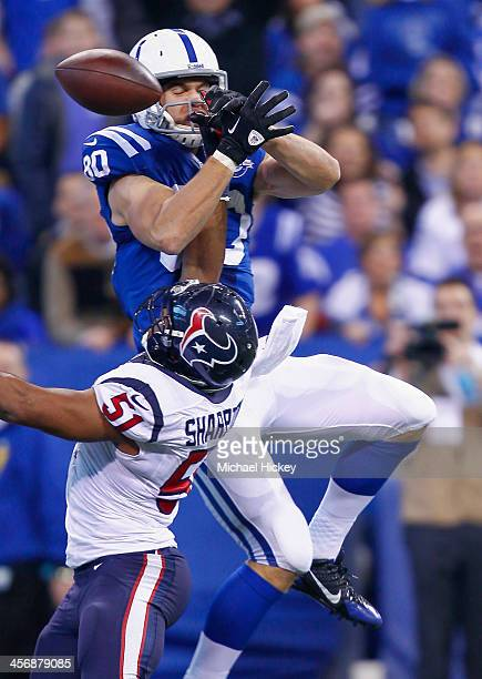 Coby Fleener of the Indianapolis Colts goes up for a pass while defended by Darryl Sharpton of the Houston Texans at Lucas Oil Stadium on December 15...