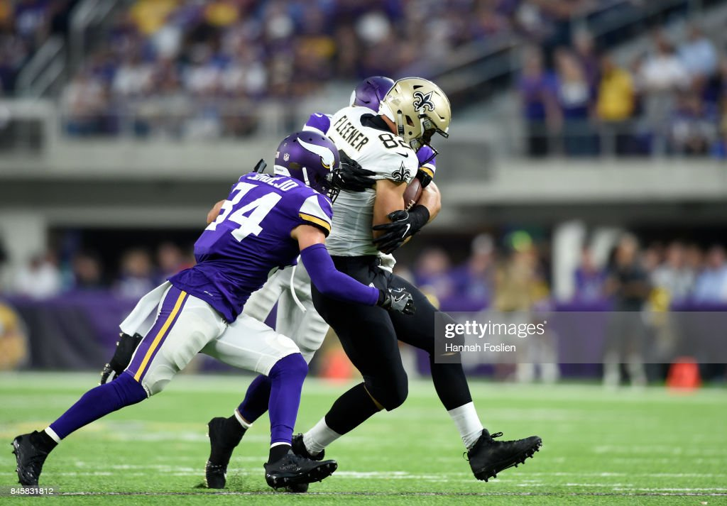 Coby Fleener #82 of the New Orleans Saints catches the ball over two defenders in the first half of the game against the Minnesota Vikings on September 11, 2017 at U.S. Bank Stadium in Minneapolis, Minnesota.