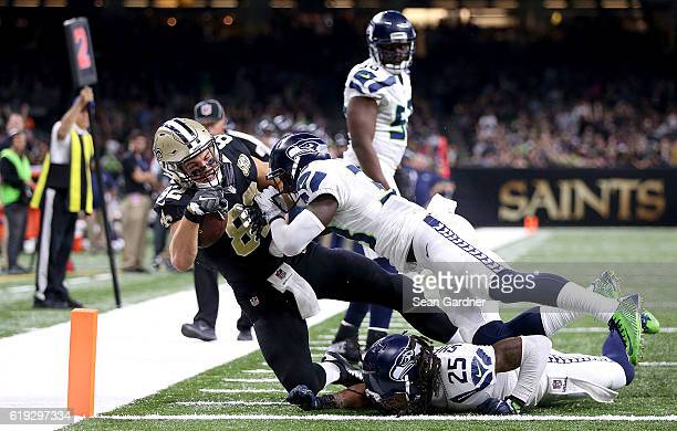 Coby Fleener of the New Orleans Saints is pushed out of bounds by Richard Sherman of the Seattle Seahawks and Kelcie McCray duirng the third quarter...