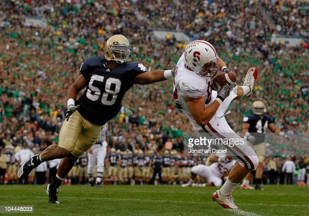 Coby Fleener of the Stanford Cardinal catches a touchdown pass as Brian Smith of the Notre Dame Fighting Irish tries to defend at Notre Dame Stadium...