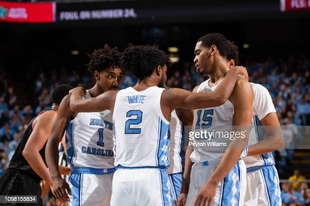 Coby White huddles and hugs teammates Leaky Black and Garrison Brooks of the North Carolina Tar Heels during a game against the Virginia Tech Hokies...
