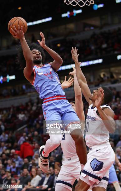 Coby White of the Chicago Bulls puts up a shot against De'Anthony Melton and Grayson Allen of the Memphis Grizzlies at the United Center on December...