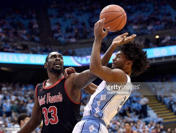 Coby White of the North Carolina Tar Heels battles Luidgy Laporal of the St Francis Red Flash for a rebound during the first half of their game at...