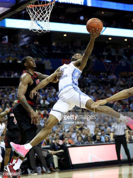 Coby White of the North Carolina Tar Heels drives to the basket against VJ King of the Louisville Cardinals during their game in the quarterfinal...