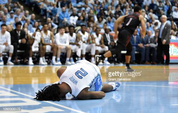Coby White of the North Carolina Tar Heels goes down in the lane after a drive to the basket against the Louisville Cardinals during the second half...
