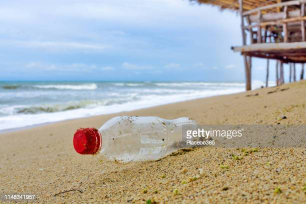coca cola plastic bottle garbage pollution on beach - water's edge stock pictures, royalty-free photos & images