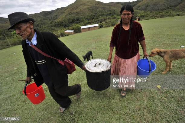 Coca grower Don Leandro Tului is helped on October 24 2013 to carry a pot across a field in Miraflores a community near the Apolo region and the...