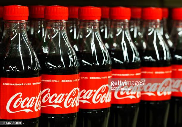Coca-Cola bottles are seen on a shelf.