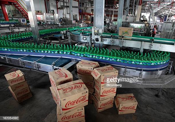 CocaCola branded boxes sit on the ground as bottles of Sprite move along a conveyor belt at a CocaCola Amatil Ltd plant in Medan North Sumatra...